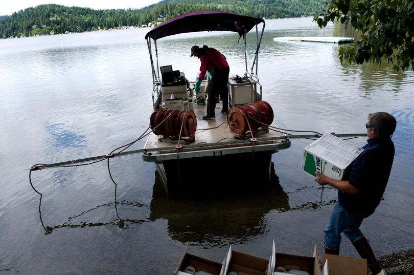 Aquatic biologist Brandon Watson loads a box of the chemical 2,4-D onto a boat equipped with outriggers designed to distribute the chemical into the water to kill Eurasian milfoil, an invasive aquatic weed, during a control effort at Newman Lake. (Tyler Tjomsland)