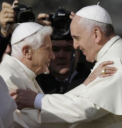 In this Sept. 28, 2014 file photo, Pope Francis, right, hugs Pope Benedict XVI prior to the start of a meeting with elderly faithful in St. Peter's Square at the Vatican. Retired Pope Benedict XVI has broken his silence to reaffirm the value of priestly celibacy, co-authoring a bombshell book at the precise moment that Pope Francis is weighing whether to allow married men to be ordained to address the Catholic priest shortage. (Gregorio Borgia / AP)