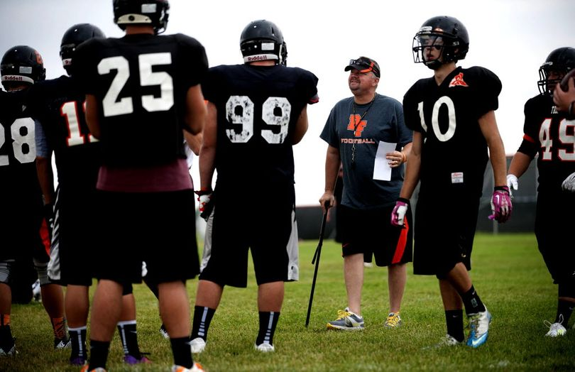 Post Falls football coach Jeff Hinz walks with the use of a cane during practice on Friday, August 15, 2014. (Kathy Plonka/SR file photo)