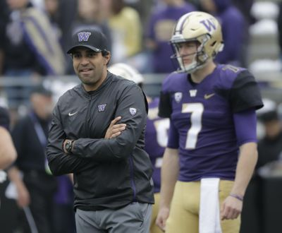 Washington offensive coordinator and quarterbacks coach Bush Hamdan, left, stands on the field during warmups before  the Oct. 20 game against Colorado  in Seattle. (Ted S. Warren / AP)
