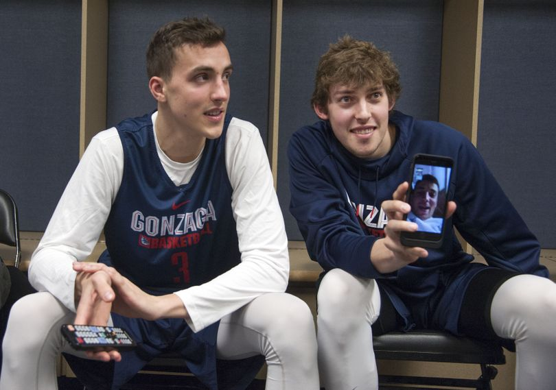 Zag players Kyle Dranginis and Kyle Wiltjer show teammates a live chat they are having with former player Kevin Pangos before practice at the Pepsi Center, March 16, 2016, in Denver, Co. The pair called Pangos in Spain. (Dan Pelle / The Spokesman-Review)