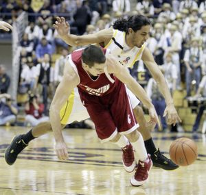 California's Jorge Gutierrez attempts to steal the ball from WSU's Taylor Rochestie during first-half play.  (Associated Press / The Spokesman-Review)