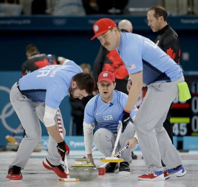 The United States' John Shuster, center, watches teammates John Landsteiner, left, and Matt Hamilton sweep the ice during the Olympic curling competition last month. (Natacha Pisarenko / AP)