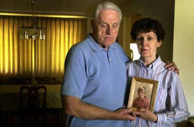 Terry and Ann Corrigan hold a picture of their son, Tim, at about the age he was allegedly sexually abused by Father Patrick O'Donnell. Corrigan committed suicide two years ago.  (Jed Conklin / The Spokesman-Review)