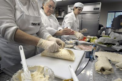 Chef instructor Vira Melendez-Redman,  center,  works with trainees including Keri Perdue,  right,  as they learn to make wraps Thursday.  Trainees learn organization, food handling,  time management, sanitation and other skills through the Transitions program at New Leaf Bakery and Café.  (CHRISTOPHER ANDERSON / The Spokesman-Review)