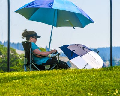 Kerrie Miles says she has her own built-in shade with a pair of umbrellas as she reads a book while her son, Logan, participates in the Skyhawks Sports Academy golf camp, Tuesday at Prairie View Park in Spokane.  (Dan Pelle/THE SPOKESMAN-REVIEW)