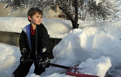 Cub Scout Jac Newman, 6, helps shovel snow off a car while clearing a driveway as a service project with the local Boy Scout community last week. (Jesse Tinsley / The Spokesman-Review)