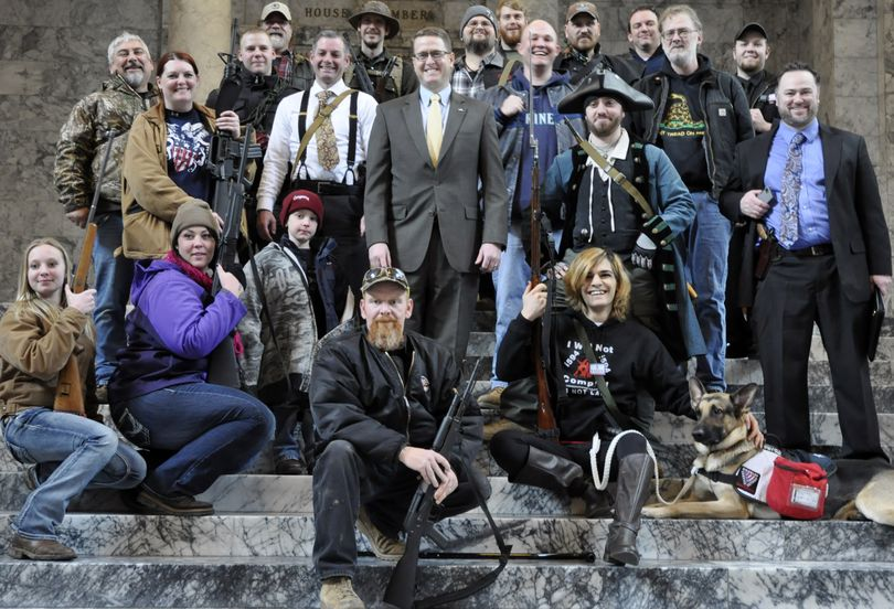 OLYMPIA -- Rep. Matt Shea, R-Spokane Valley, poses with gun rights activists on the steps outside the House Chambers after speaking at a rally against I-594 on Thursday, 1/15/2015. The activists had come into the Capitol to lobby legislators but were told they couldn't come on the House floor. (Jim Camden)