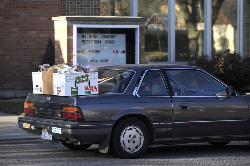 A client pulls away from the mobile food bank Friday, Dec. 11, 2009 at Millwood Presbyterian Church with their portion of groceries stacked on the trunk lid.  The person only lived a block away.  At mobile food banks, the portions are generous and there is no qualifying for eligibility. The church has committed to holding a food drop every month at the church.  Second Harvest provides the food when a group volunteers to hold one. (Jesse Tinsley / The Spokesman-Review)