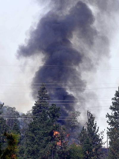 A fire burns on a ridge in an area of rural homes near North Harvard Road on Friday. The fire was under control as of 4 p.m., a fire dispatcher said. (Jesse Tinsley)