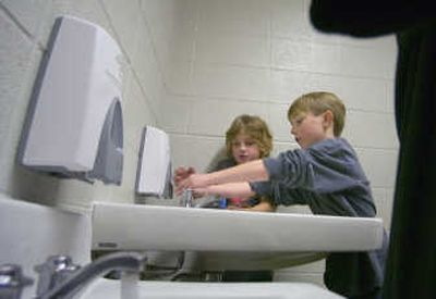 Tiras Wilbur, left,  and Marcus Holland  wash their hands after coming in from the playground Friday at Audubon Elementary School. Recent reports of MRSA cases in schools across Washington state have sparked sanitizing efforts.     (CHRISTOPHER ANDERSON / The Spokesman-Review)