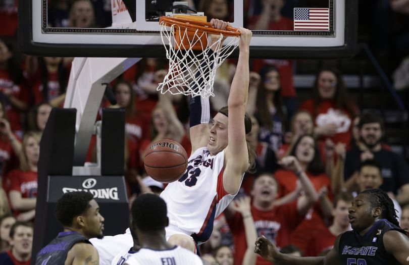 GU's Kelly Olynyk hangs on the rim after dunking in the first half. Olynyk, with four dunks, scored 20 points. (Associated Press)