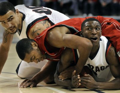 Gonzaga's Demetri Goodson tries to call time out as Mississippi Valley's #15 Shannon Behling ties up the ball in the 1st half, November 14, 2009 at the McCarthey Athletic Center.  Zag's Robert Sacre (rear) also hits the floor. (Dan Pelle / The Spokesman-Review)