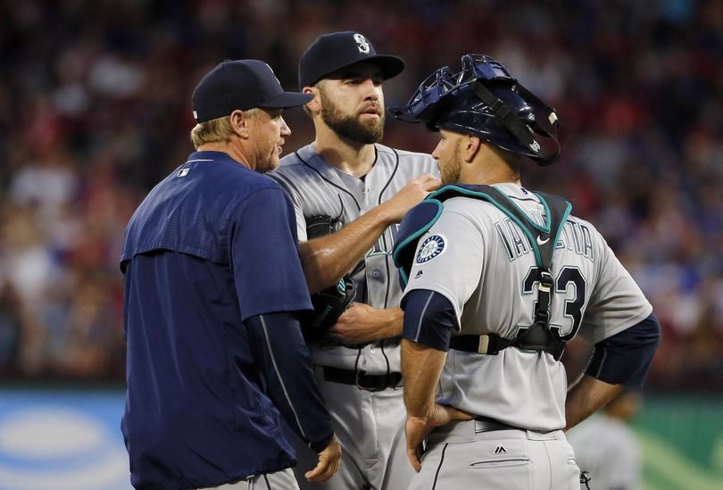The Seattle Mariners are hoping a return to familiar settings in Tampa Bay will help pitcher Nathan Karns, center with pitching coach Mel Stottlemyre and catcher Chris Iannetta, regain his earlier form. (Tony Gutierrez / Associated Press)