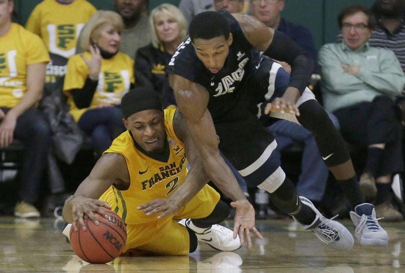 San Francisco forward Uche Ofoegbu, left, reaches for a loose ball under Gonzaga guard Eric McClellan during the first half of an NCAA college basketball game in San Francisco. (Jeff Chiu / Associated Press)