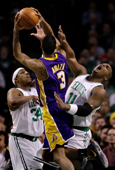 Trevor Ariza, center, fights for a basket in the latest Lakers-Celtics clash. (Associated Press / The Spokesman-Review)