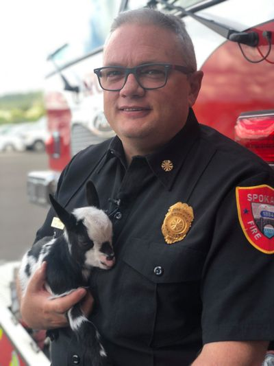 Spokane Fire Chief Brian Schaeffer holds a young goat in this photo shared on the department's Facebook page.  (Adam Shanks / The Spokesman-Review)