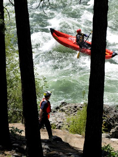 A Spokane Fire Department rescuer scours the Spokane River  after an empty raft was found Monday downstream of the Bowl and Pitcher. The rafter later turned up safe. colinm@spokesman.com (COLIN MULVANY colinm@spokesman.com / The Spokesman-Review)