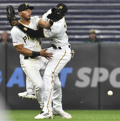 Pittsburgh Pirates shortstop Erik Gonzalez, left, and center fielder Starling Marte collide going for a ball hit by San Francisco Giants' Yangervis Solarte during the eighth inning of a baseball game Friday, April 19, 2019, in Pittsburgh. (Matt Freed / Pittsburgh Post-Gazette via AP)