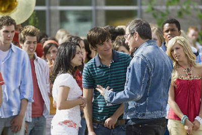 In this photo released by the Disney Channel, cast members listen as actors Vanessa Anne Hudgens, in white, and Zac Efron speak with director Kenny Ortega on the set of