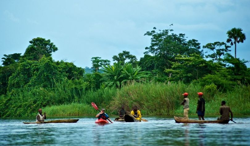 In this undated photo provided by Eddie Bauer First Ascent, South African kayaker Hendri Coetzee, center, paddles on the Lukuga River in Congo with local villagers. On Dec. 7, 2010, Coetze was ripped from his kayak, never to be seen again, on the same river on an expedition with two Americans.  (Chris Korbulic / Eddie Bauer First Ascent)