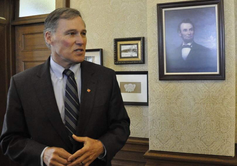 OLYMPIA -- Gov. Jay Inslee shows off the changes to the governor's office, including a portrait of Abraham Lincoln given to him by his father-in-law. (Jim Camden)