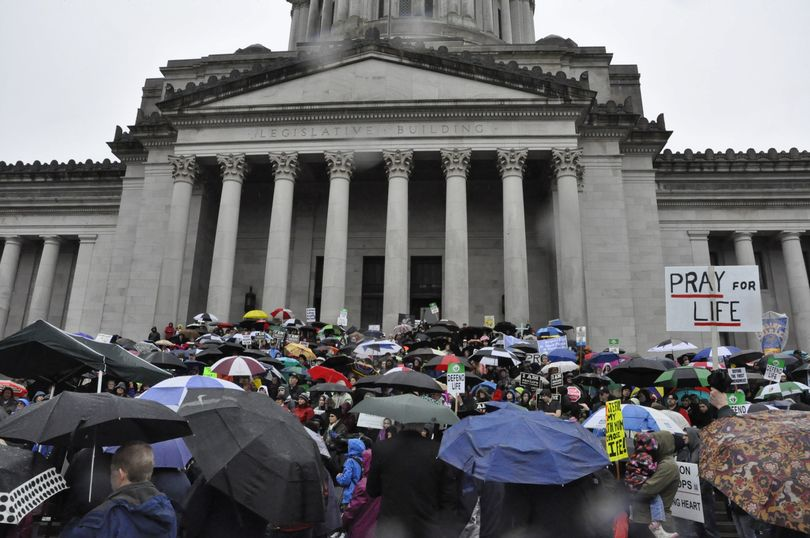 OLYMPIA -- Members of the annual March for Life gather under umbrellas on the north steps of the state Capitol. (Jim Camden/The Spokesman-Review)