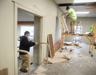 Tod Davin, of Krueger Sheet Metal, left, works on a stairway hand rail, and Garth Seay, of Energized Electric, opens a stack of ceiling tile while finishing the first two rooms at the Cannon Street shelter, Friday, Oct. 30, 2020, near downtown Spokane. A third room will be completed in December. DAN PELLE/THE SPOKESMAN-REVIEW  (DAN PELLE/THE SPOKESMAN-REVIEW)