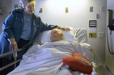 Jackie Volz visits with her 100-year-old father, Richard Hubbard, on Friday. He was recovering from heart surgery at Deaconess Medical Center.   (Christopher Anderson / The Spokesman-Review)