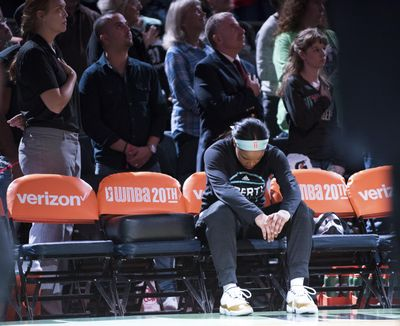 Brittany Boyd of the Liberty sits on the bench with her head bowed during the national anthem before New York's game  against the Phoenix Mercury on Saturday. (Cooper Neill / Associated Press)