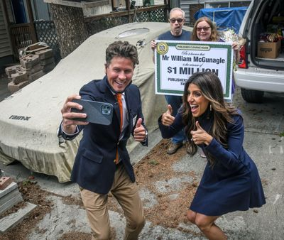 Howie Guja, left, and Danielle Lam, of the Publishers Clearing House Prize Patrol, take a picture Friday after awarding a $1 million prize to William McGunagle and his wife, Kat, both of Spokane.  (DAN PELLE/THE SPOKESMAN-REVIEW)