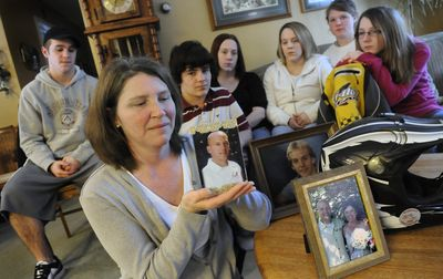 Sue Smith holds a picture of her husband, Rob, on Tuesday at his parents' home near Colbert. Rob Smith  died Friday in a snowmobile accident. Behind Smith are, from left: Rob Smith's son Ryan Smith; his stepson Cameron Moors; his daughters Shea Smith and Erica Cease; and Sue Smith's daughters Sara Overfelt and Emily Overfelt.   (Dan Pelle / The Spokesman-Review)