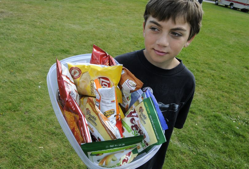 Jon Coggin, 10, sells chips for $1 to raise money for Carissa Outen on May 19, 2010, at the Spokane Community College Spring Fling Car Show. (Dan Pelle / The Spokesman-Review)
