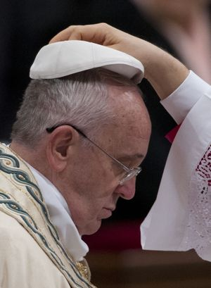 Pope Francis is helped wearing his skull cap as he arrives to celebrate the new year's eve vespers Mass in St. Peter's Basilica at the Vatican, Wednesday, Dec. 31, 2014. The traditional Mass on Dec. 31contains the thanksgiving hymn ''Te Deum' for the ending year and is the last public appearance of the pope in 2014. (Andrew Medichini / Associated Press)