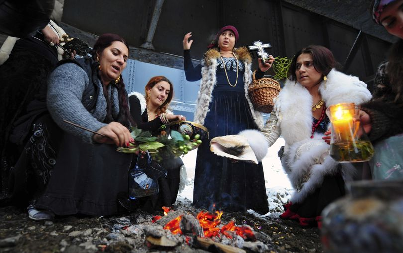 Romanian witches perform a ritual in Chitila, Romania, on Thursday to celebrate Epiphany, gathering around a fire and throwing corn into an icy river. (Associated Press)