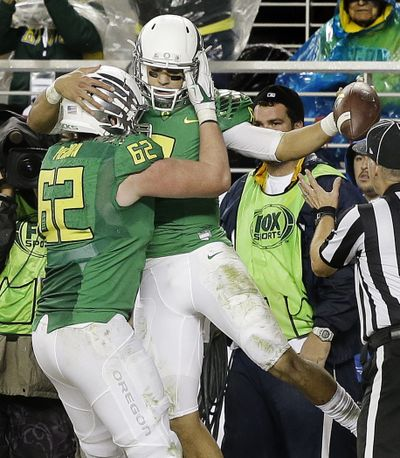 Oregon's Marcus Mariota, right, and Matt Pierson celebrate after Mariota scored one of his three touchdowns. (Associated Press)