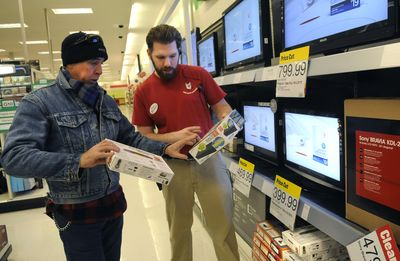 Target employee Andrew Sawatzki helps Eddie Stazel, of Spokane Valley, select a digital TV converter box Wednesday at the Valley store. Stazel used a federal coupon for one box and said he would apply for two more.  (Dan Pelle / The Spokesman-Review)