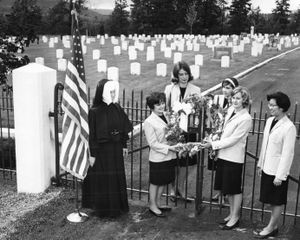 """In this 1965 photo, Fort George Wright College students remember Veterans at the cemetery. Friday was """"memorial"""" day for a group of Fort Wright College students who wanted to be certain the men buried in the historic Fort Wright Cemetery were not forgotten in this season. School will be out before the generally observed Memorial Day. Seen at the rites arranged by Spurs, a sophomore group, were Sister Victor Maria, Carol Perry, Caroline Dorscheid, Rita Cavanaugh, Laura Fitzpatrick and Jean Otani. (Photo Archives/spokesman-review)"""