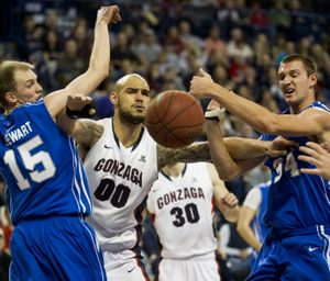 Chasing a rebound, Gonzaga center Robert Sacre (00) parts the way between Air Force guard Taylor Stewart (15) and center Taylor Broekhuis (34) during the first half of their NCAA college basketball game Thursday, Dec. 22, 2011, in the McCarthey Athletic Center in Spokane, Wash. COLIN MULVANY colinm@spokesman (Colin Mulvany / The Spokesman-Review)