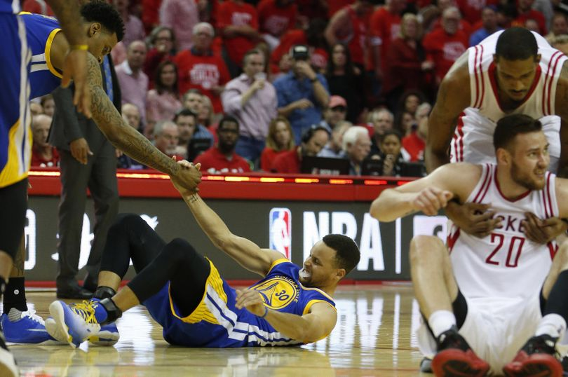 In this Sunday photo, Golden State Warriors guard Stephen Curry (30) is helped up after being injured on the final play during the first half of Game 4 in the first round of the NBA playoff series against the Houston Rockets. (Karen Warren / Associated Press)