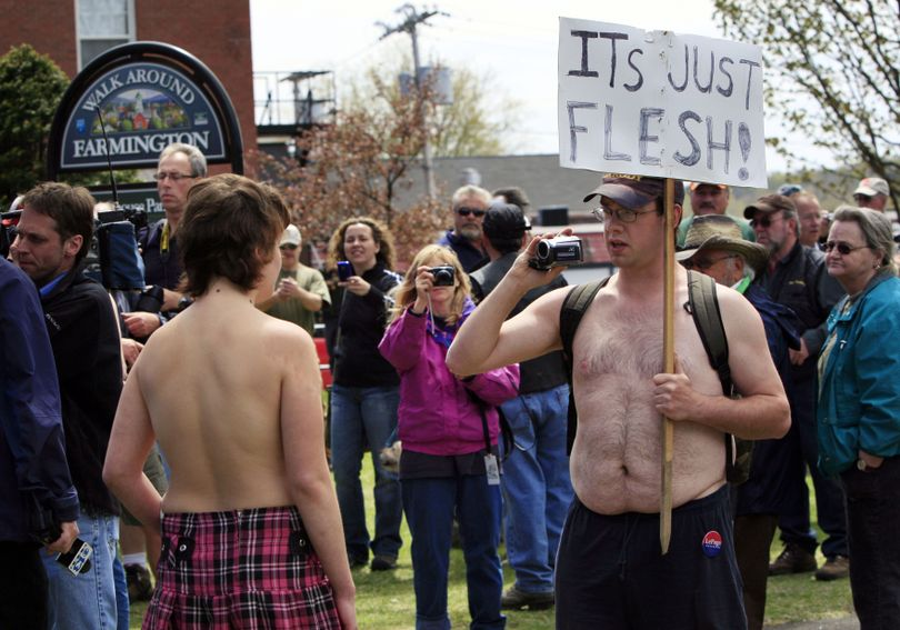 University of Maine at Farmington student Andrea Simoneau, left, is videotaped during a topless protest Friday, April 30, 2010, in Farmington, Maine. The demonstration called attention to the double-standard that it's acceptable for men, but not women, to go bare chested. In Maine, it's perfectly legal for women to go topless in public. (Robert Bukaty / Associated Press)