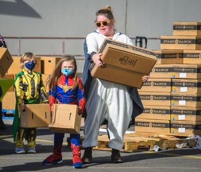 Dressed for the season, from left, Josephine Kulland, 4, as Marvel character Loki, Georgiana Gewock, 7, as Captain America and Rachael Gewock as a flying squirrel, participate in delivering food boxes to arriving vehicles Friday at 11016 E. Montgomery Drive in Spokane Valley.  (DAN PELLE/THE SPOKESMAN-REVIEW)