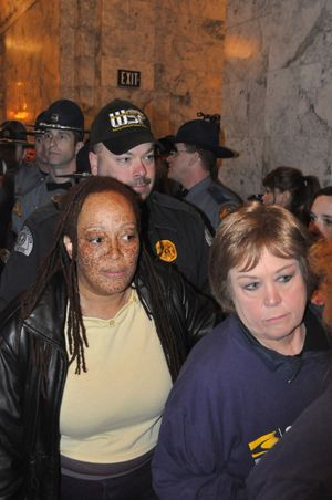 Karen Washington, left, of Spokane is among protesters arrested by the Washington State Patrol outside the governor's office on Thursday, April 7.
