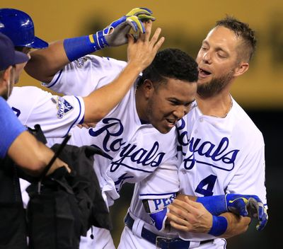 Kansas City Royals Whit Merrifield, left, and Alex Gordon, top right, congratulate teammate Salvador Perez, middle, after his winning two-run double during the ninth inning Thursday against visiting Seattle. (Orlin Wagner / Associated Press)