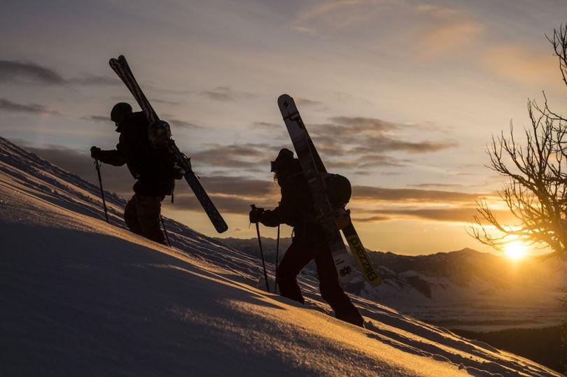 Skiers climb to reach a high point for a run. (Associated Press)