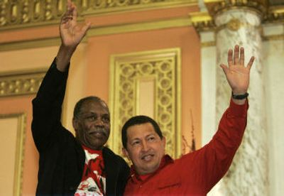 Venezuelan President Hugo Chavez, right, and actor Danny Glover wave to a crowd gathered at the Mount Olivet Baptist Church in the Harlem neighborhood of New York on Thursday.   (Associated Press / The Spokesman-Review)
