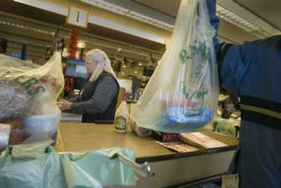 Shoppers at the Rosauers in Browne's Addition can now have their purchases bagged in paper or the new green-tinted Eco Hippo plastic bags. Sarah Tupper loads up a bag while checker Ardi Stanhop finishes the transaction.   (Christopher Anderson / The Spokesman-Review)
