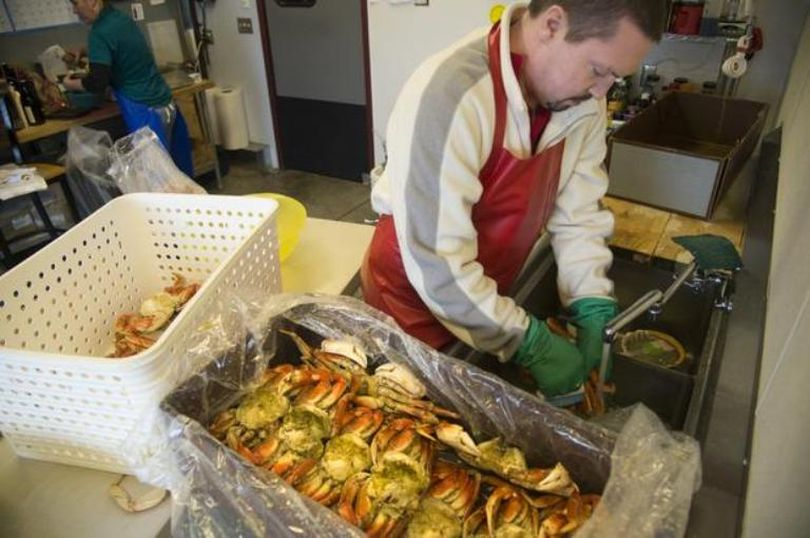 Shawn Offield carefully cleans steamed Dungeness crabs to fill special orders in the back room at Williams Seafood, which is owned by the Offield family, Tuesday, Dec. 22, 2015. The price for crab products is up this year with a shortage of some types of crabs. Owner Mike Offield said they've kept their margins the same, but raised their prices according to their costs. (Jesse Tinsley / The Spokesman-Review)