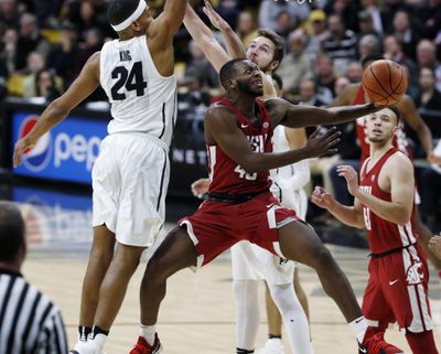 Washington State guard Kwinton Hinson drives the lane for a basket between Colorado guard George King, back left, and forward Lucas Siewert on Jan. 18 in Boulder, Colorado. (David Zalubowski / AP)