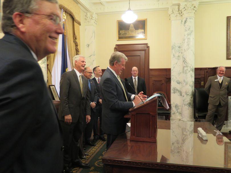 Gov. Butch Otter signs his first bill into law of the 2018 Idaho legislative session on Wednesday, Jan.n 31, 2018; at left is House Speaker Scott Bedke; at center, Senate President Pro-Tem Brent Hill. (Betsy Z. Russell)